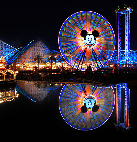 Ferris wheel with Mickey Mouse face lit up at night
