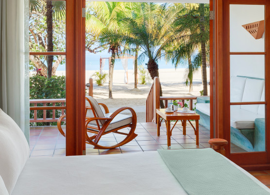 a veranda with chairs and a beach view