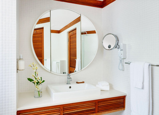 a bathroom vanity with large round mirror and wood accents