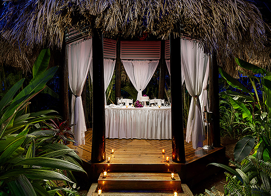 a private dinner in a gazebo secluded with white curtains at night