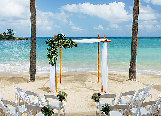 an ocean front beach wedding ceremony set with with a small gazebo draped with white tulle