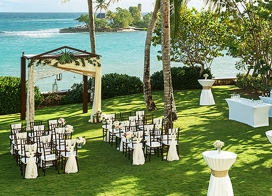 small wedding ceremony set up on a lawn overlooking the ocean