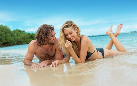 man and woman laying on their stomachs in the shallow beach water