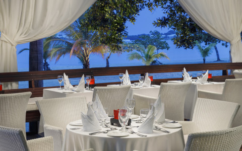 outdoor balcony seating at a restaurant with white chairs and tablecloths over tables