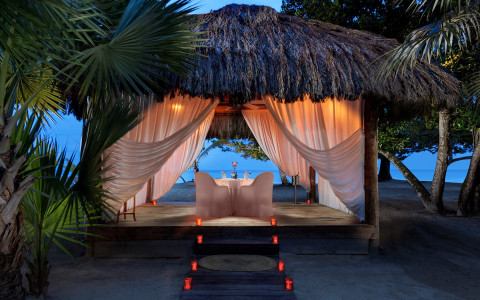 private dining table under a tiki hut on the beach at night