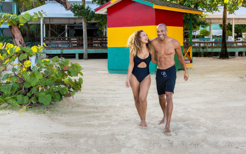 couple walking on the beach in front of a colorful shack