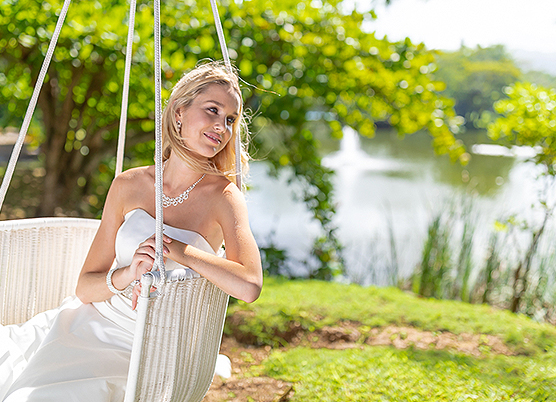 bride sitting in a wicker swing outside