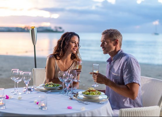 a man and woman having a romantic dinner on the beach