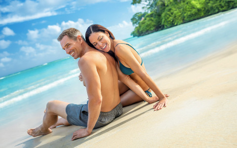 woman leaning against man while sitting together on the beach near the water line