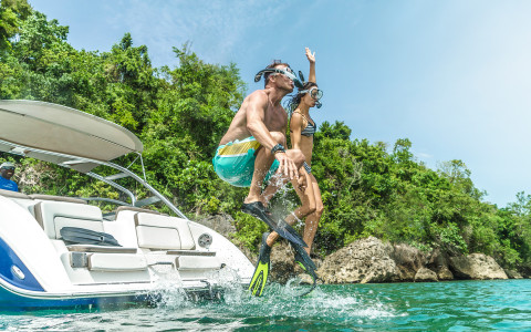 couple wearing snorkeling gear jumping into the ocean from a boat