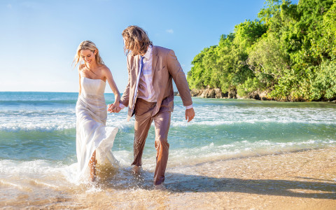 bride and groom holding hands walking through the ocean water on the beach