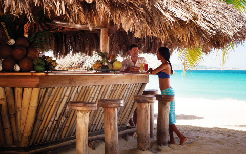 couple standing at a tiki bar on the beach