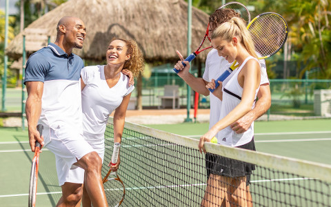 two couples on the tennis court laughing together