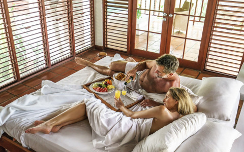 man and woman having breakfast in bed