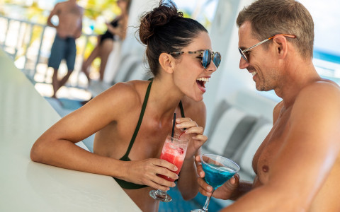 couple having cocktails at a pool bar