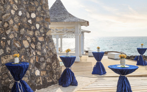 cocktail tables draped in navy tablecloths near a white gazebo overlooking the ocean