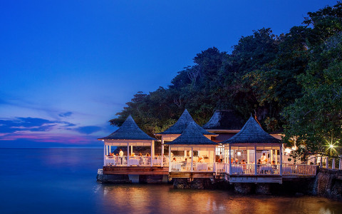 outdoor restaurant with several gazebos on the water at night
