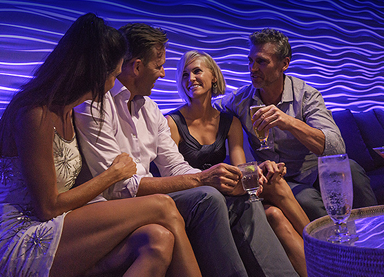 two couples sitting together at a dimly lit bar drinking