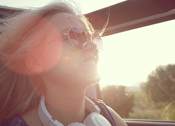 woman riding in a car with the sun gleaming behind her