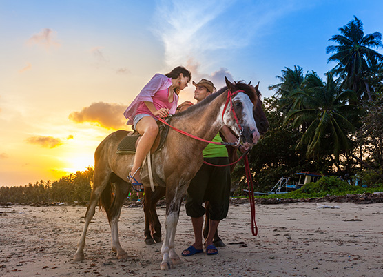 a woman sitting on a horse on the beach looking at a man standing next to her at sunset