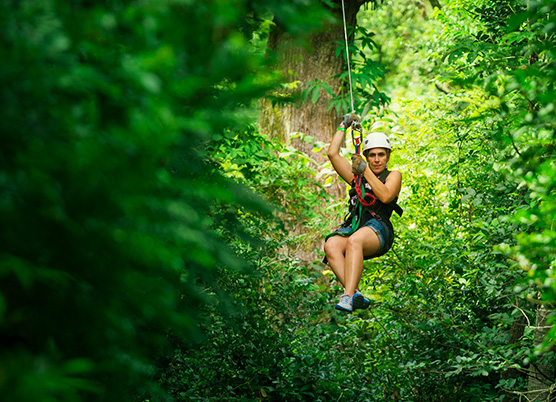 a woman ziplining through trees