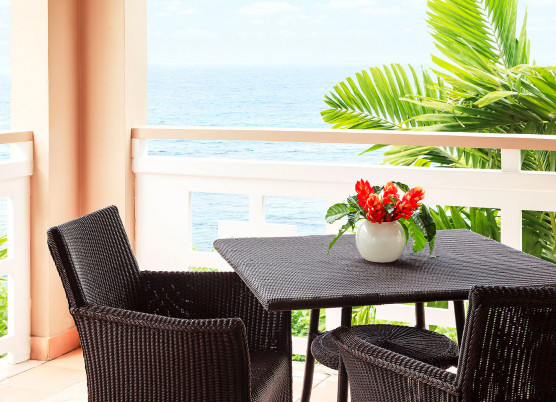 guest room balcony with dark wicker table and chairs with ocean view