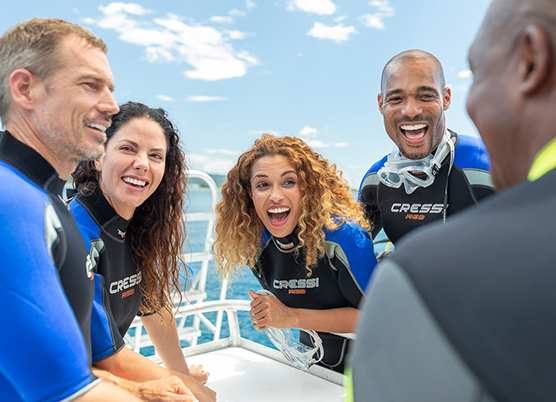 two couples on a boat wearing wetsuits