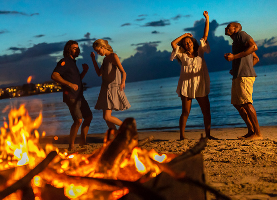 a group of friends dancing near a campfire on the beach at night