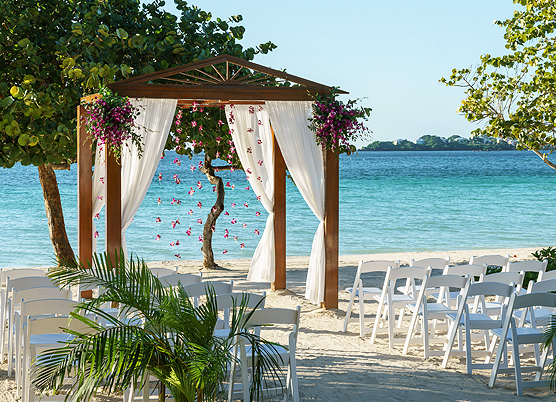 a wedding ceremony set up on the beach with a wooden gazebo draped with white curtains