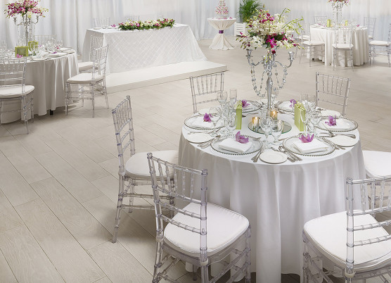 indoor wedding reception with round white tablecloth tables with centerpieces