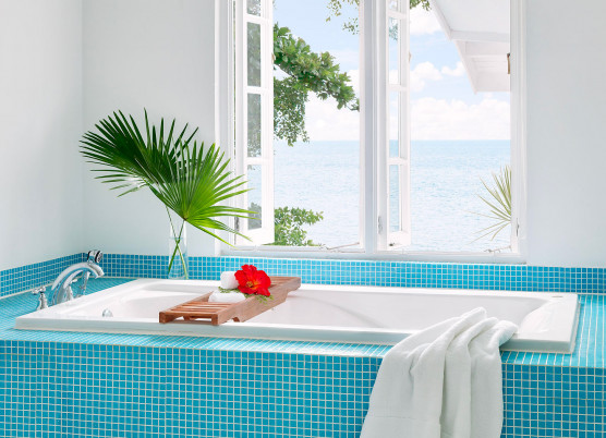 hibiscus cottage with blue tile bath tube with a window above overlooking the ocean