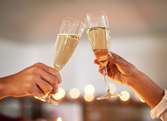 close up of a couple holding out glasses of champagne for a toast