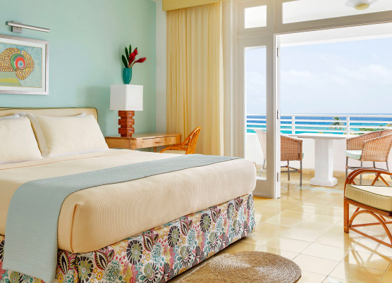 guest room with light yellow and light blue accent colors and a balcony area overlooking the ocean