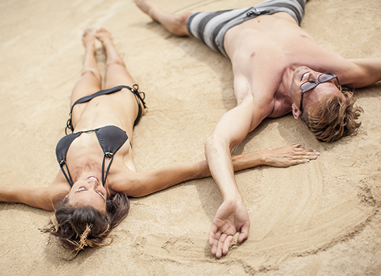 couple at the beach laying in the sand with their arms stretched out to the side