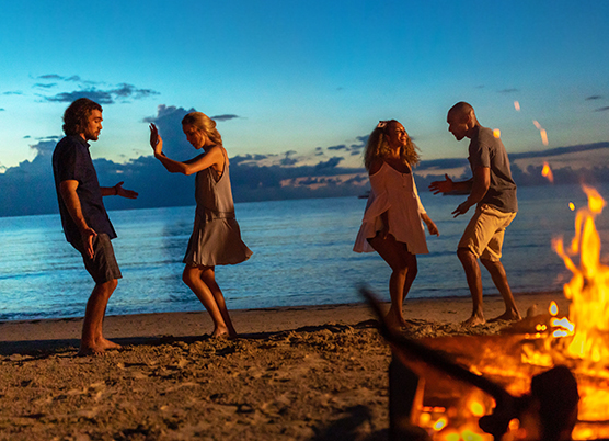 two couples dancing at a beach bonfire at night