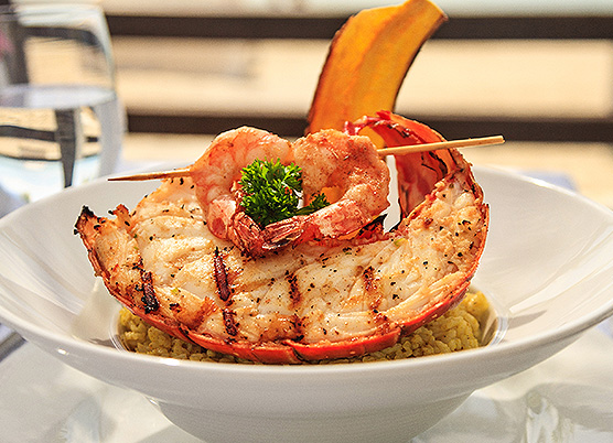 lobster topped with shrimp in a bowl of rice