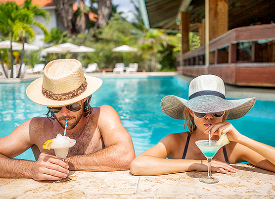 couple leaning on edge of pool with drinks