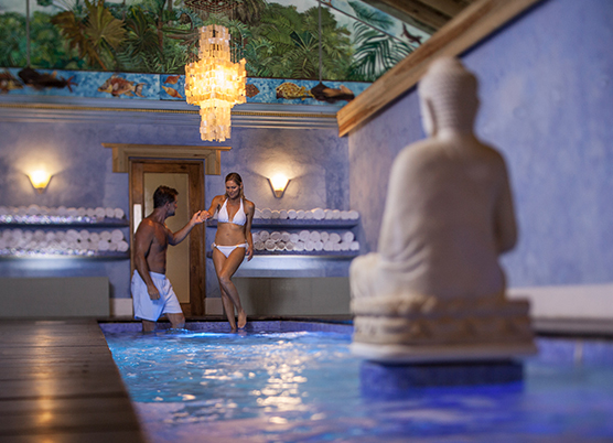 man and woman walking into indoor pool with back of statue to the camera