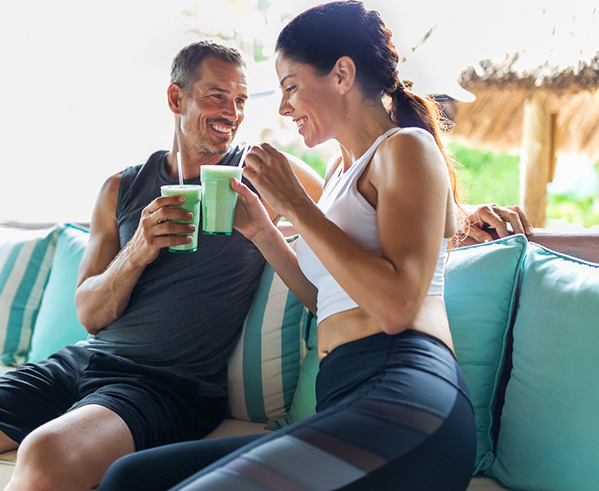 man and woman in work out clothes drinking green smoothies