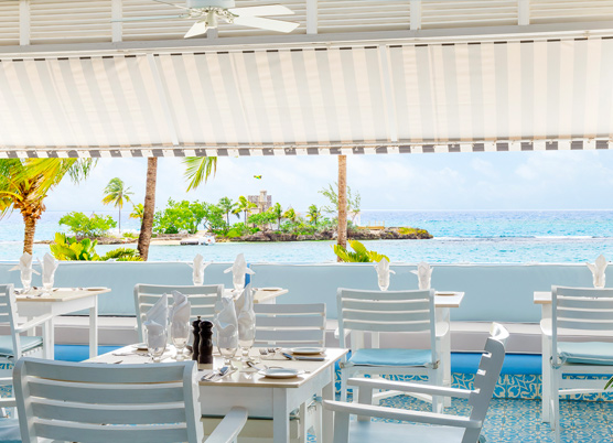 striped awning covering a casual patio dining area overlooking the ocean