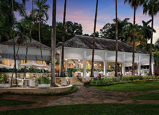 long white gazebo set up with dining tables underneath at sunset