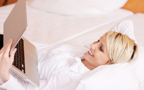 woman laying down looking at laptop