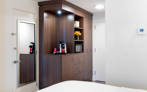 Cabinet with door that has mirror on it and the corner of the bed