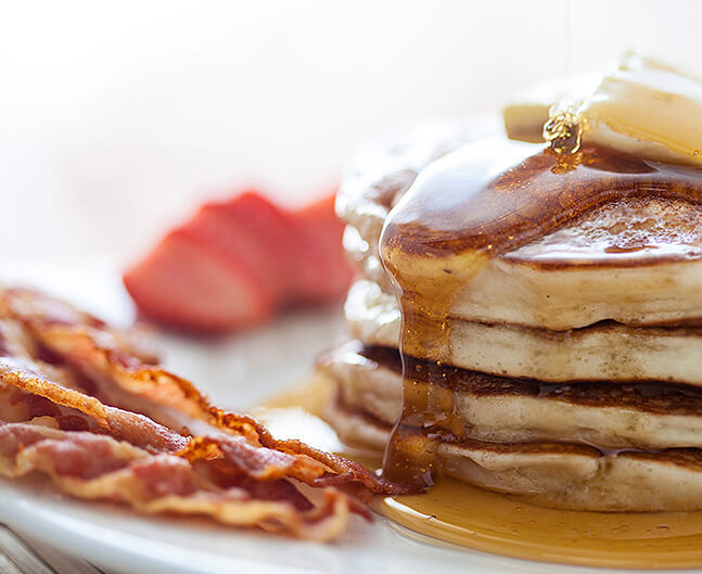 A stack of pancakes with butter and bacon on the side