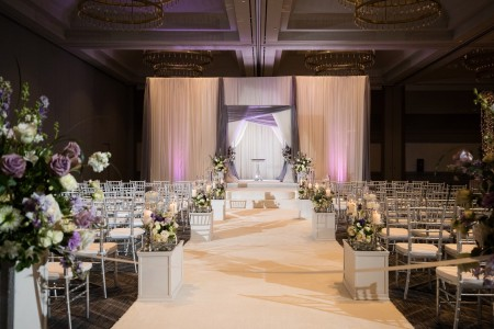 Wedding aisle decorated with white and purple flowers