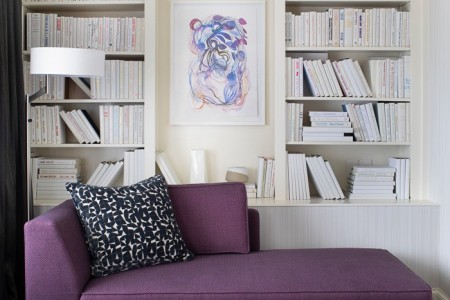 small purple couch near book shelf