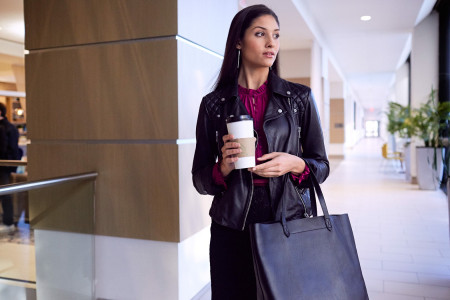a woman walking in a hallway holding her purse and coffee to go cup