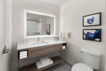 bathroom with an illuminated mirror, large vanity area with shelf storage below filled with towels