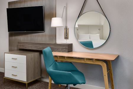 desk area with a turquoise cushioned chair, hanging round mirror, and a tv and drawer storage to the side