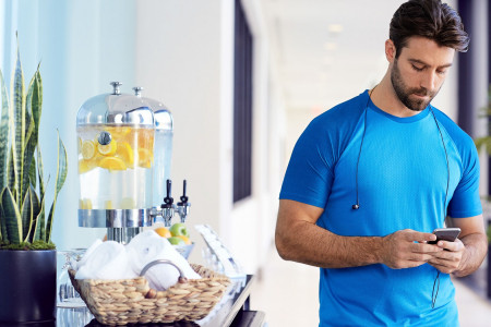 an athletic man with headphones around his neck walks next to a water station with towels and fruit water